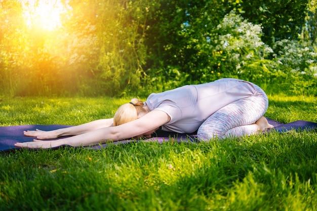 Jonge vrouw doet yoga asana in park meisje stretching oefening in yoga positie gelukkige gezonde vrouw