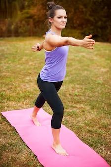 Jonge vrouw doet yoga buiten. deze positie lijkt misschien eenvoudig