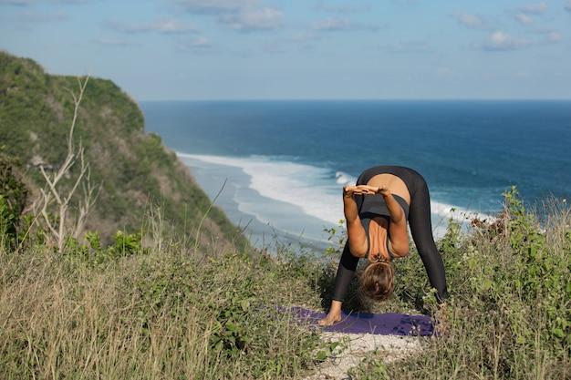 Jonge vrouw doet yoga buitenshuis met geweldig achteraanzicht. bali. indonesië.