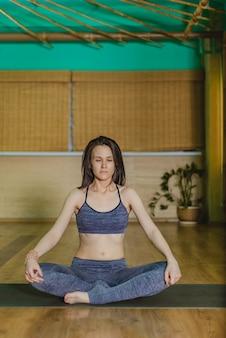 Jonge vrouw doet yoga in de lotushouding