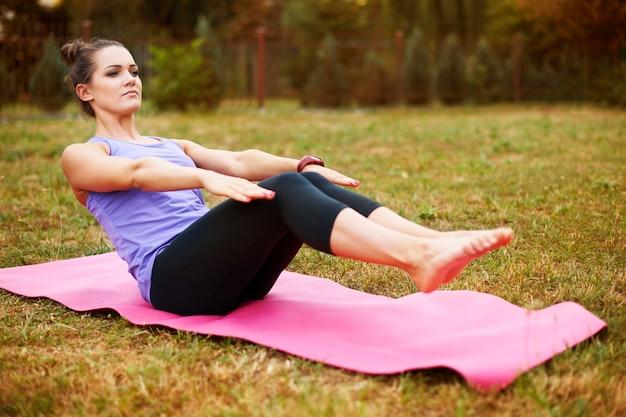 Jonge vrouw doet yoga in het park. goed rekken helpt om spierpijn te voorkomen