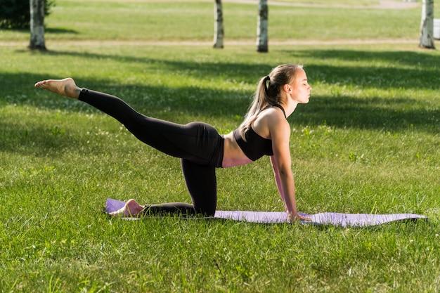 Jonge vrouw doet yoga in het park