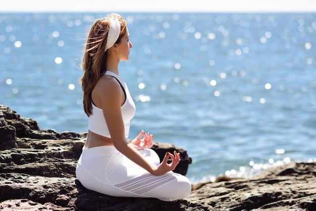 Jonge vrouw doet yoga in het strand met witte kleding