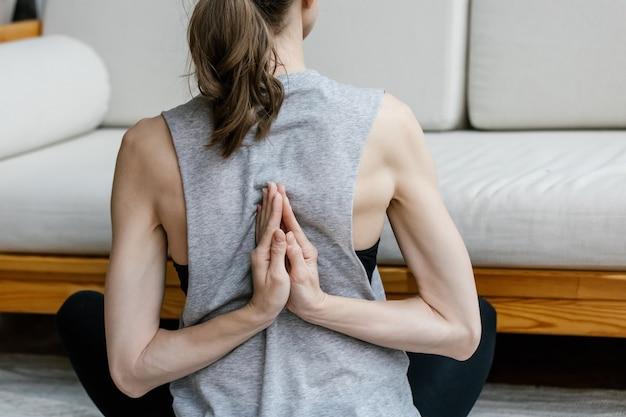 Jonge vrouw doet yoga in oefening thuis zitten