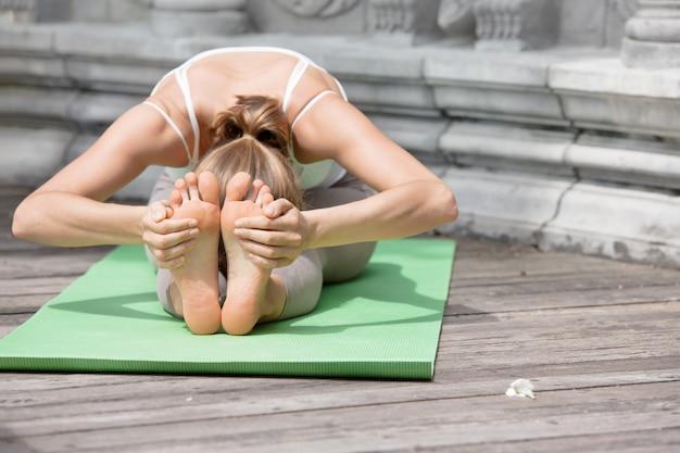 Jonge vrouw doet yoga in verlaten tempel op houten platform. oefenen in thailand