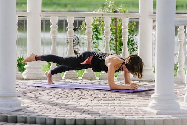 Jonge vrouw doet yoga in zomerhuis in de zomer