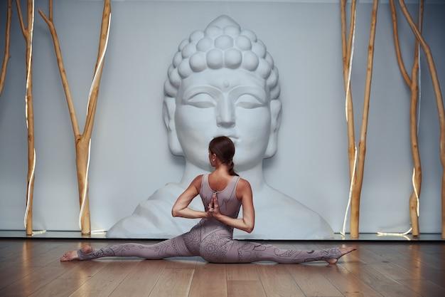 Jonge vrouw doet yoga oefening in de studio
