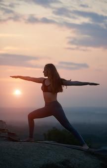 Jonge vrouw doet yoga oefeningen buiten bij zonsondergang