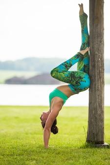 Jonge vrouw doet yoga oefeningen in zomer stadspark