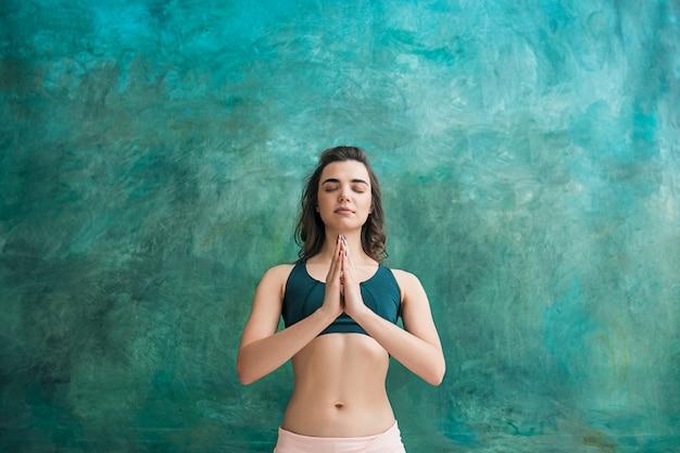 Jonge vrouw doet yoga oefeningen op groene muur