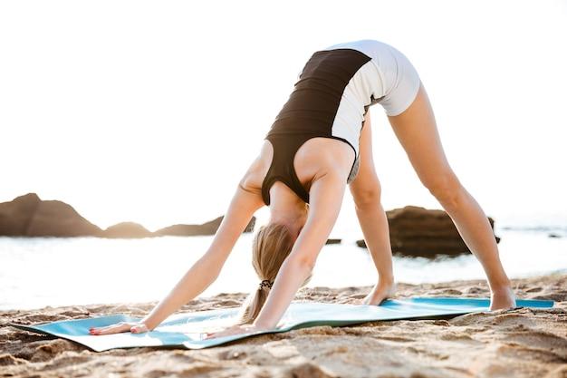 Jonge vrouw doet yoga-oefeningen op yogamat op het strand in de ochtend