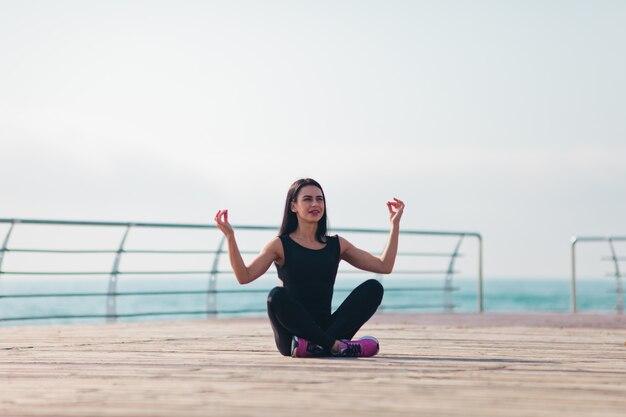 Jonge vrouw doet yoga op het strand