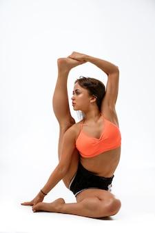 Jonge vrouw doet yoga op wit, gezondheidsconcept