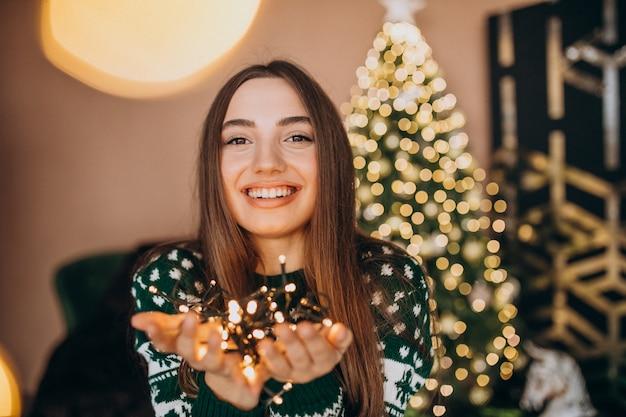 Jonge vrouw door de kerstboom met kerstmis gloeiende lichten