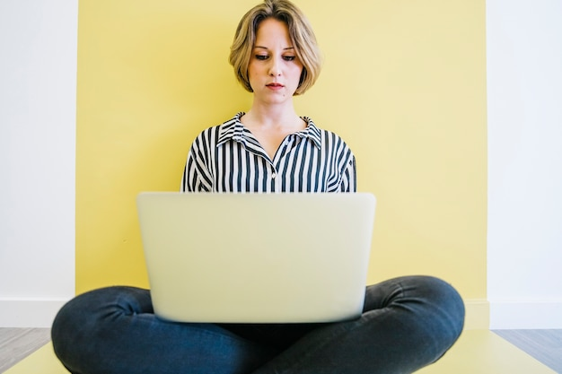 Jonge vrouw doorbladert laptop op vloer