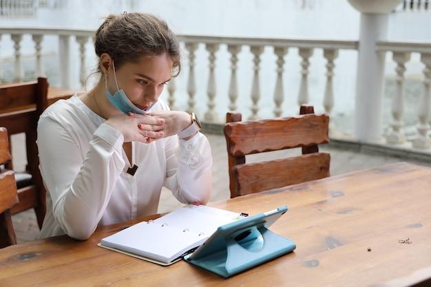 Jonge vrouw doordachte zittend aan tafel met tablet