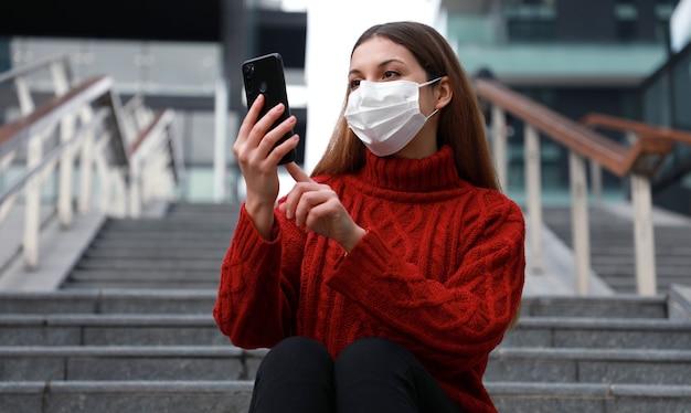 Jonge vrouw draagt beschermend masker zittend op de trap met behulp van smartphone.