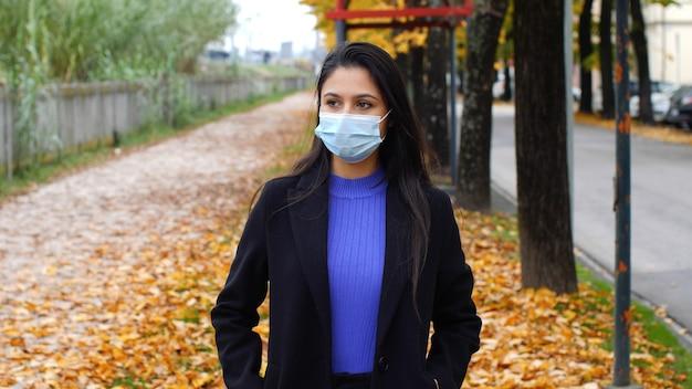 Jonge vrouw draagt chirurgisch masker in de tijd van de covid-19-pandemie. herfst landschap met bomen en vallende bladeren.