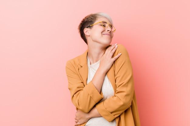 Jonge vrouw draagt een casual zakelijke kleding knuffels, glimlachend zorgeloos en gelukkig