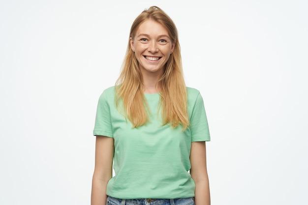 Jonge vrouw, draagt een groen t-shirt en een spijkerbroek, voelt zich gelukkig, glimlacht breed met een tevreden gezichtsuitdrukking