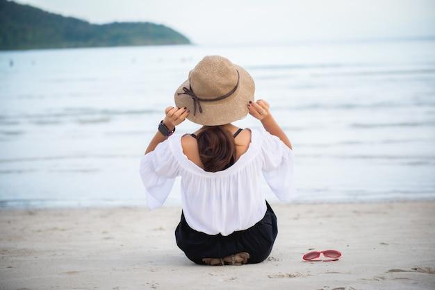 Jonge vrouw draagt een hoed zittend op het strand met uitzicht op zee en heeft een bril aan de zijkant.