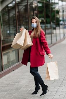 Jonge vrouw draagt een masker om virus te voorkomen met boodschappentassen op smalle straat in europa.