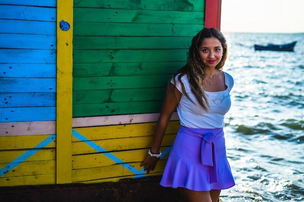 Jonge vrouw draagt een paarse rok en poseert tegen een kleurrijk gebouw omringd door de zee