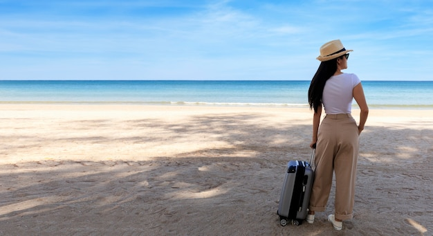 Jonge vrouw draagt een t-shirt, een lange broek en een strooien hoed met een koffer op een tropisch strand.