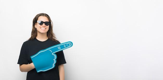 Jonge vrouw draagt een zonnebril, een handschoen van schuimventilator en wijst opzij.