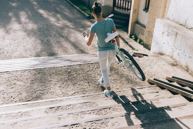 Jonge vrouw draagt haar fiets op de trap