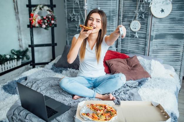Jonge vrouw draagt in casual stijl zittend op bed met pizza en laptop en zet de tv aan.