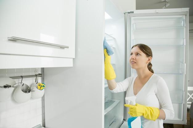 Jonge vrouw draagt rubberen handschoenen die de koelkast schoonmaken