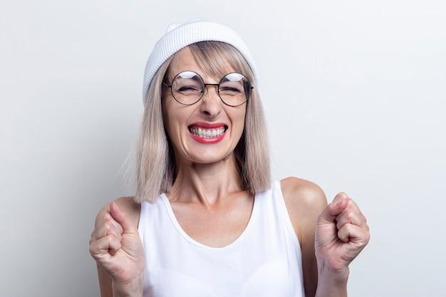 Jonge vrouw draaide haar vuisten in een witte hoed en bril op een lichte achtergrond.