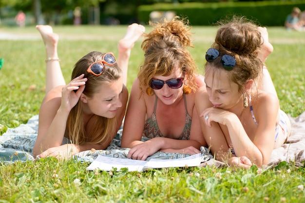 Jonge vrouw drie op het strand die een tijdschrift lezen