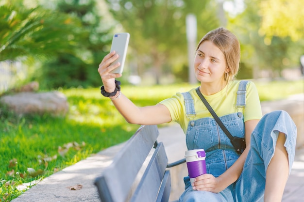 Jonge vrouw drinkt koffie in het park, ontspant, terwijl haar foto wordt gemaakt.