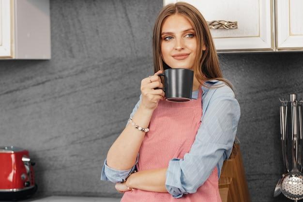 Jonge vrouw drinkt thee terwijl je in de keuken staat