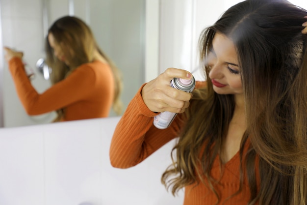 Jonge vrouw droge shampoo toe te passen op haar haar