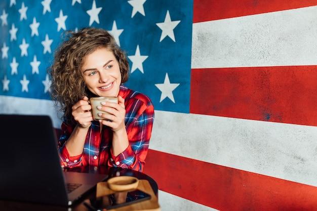 Jonge vrouw droomt over iets terwijl ze zit met een draagbaar netbook in een moderne café-bar.