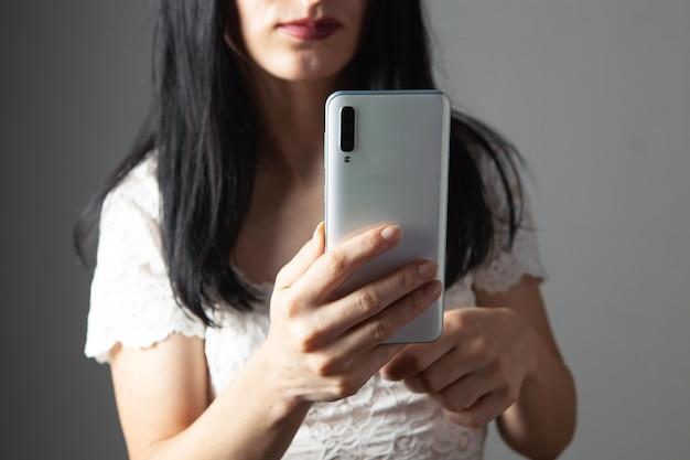 Jonge vrouw drukt op het telefoonscherm op een grijze achtergrond