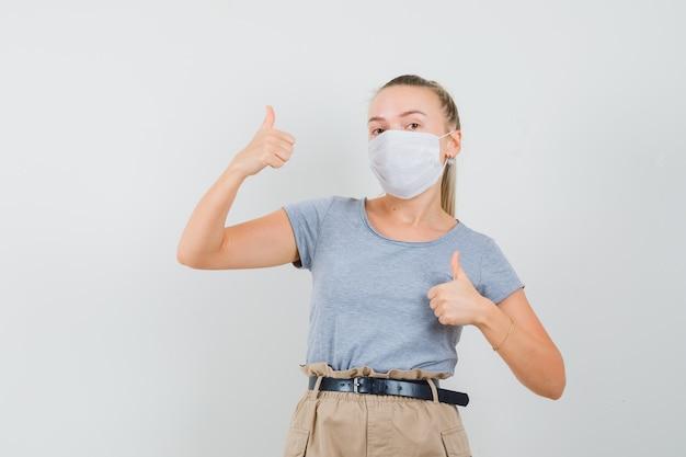 Jonge vrouw dubbele duimen opdagen in t-shirt, broek, masker vooraanzicht.