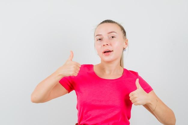 Jonge vrouw dubbele duimen opdagen in t-shirt en vrolijk kijken