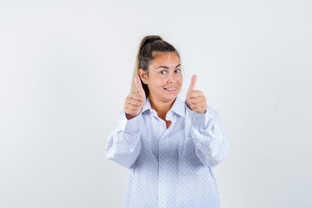 Jonge vrouw dubbele duimen opdagen in wit overhemd en vrolijk kijken