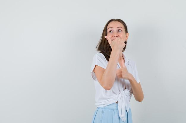 Jonge vrouw dubbele duimen opdagen in witte blouse en lichtblauwe rok en vrolijk kijken