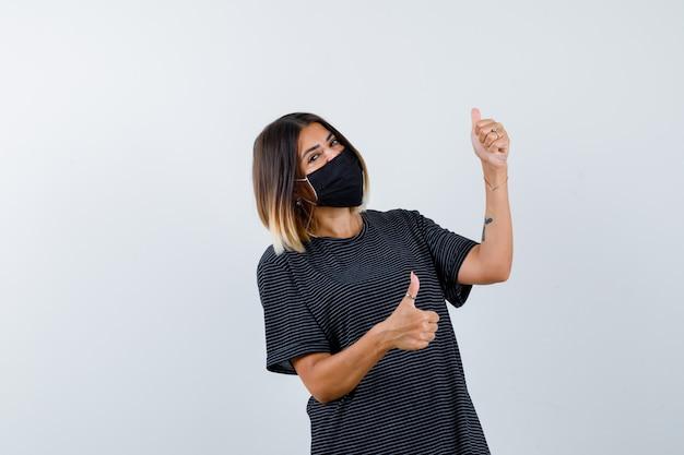Jonge vrouw dubbele duimen opdagen in zwarte jurk, zwart masker en op zoek gelukkig, vooraanzicht.