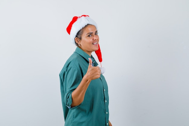 Jonge vrouw duim opdagen in shirt, kerstmuts en er gelukkig uitzien.