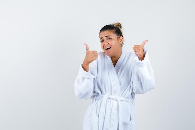 Jonge vrouw duimen opdagen in badjas en er gelukkig uitzien
