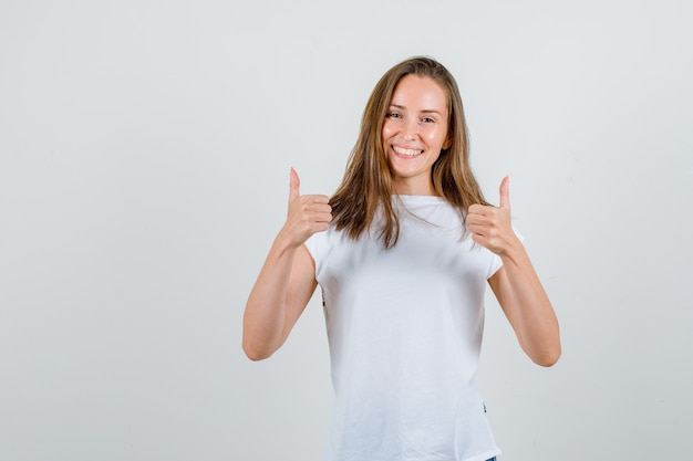 Jonge vrouw duimen opdagen in t-shirt en op zoek gelukkig. vooraanzicht.
