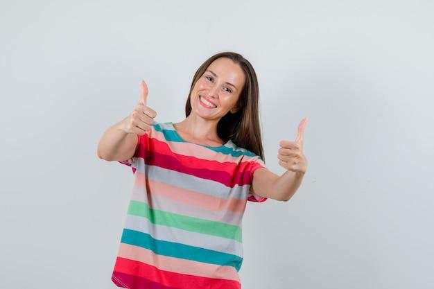Jonge vrouw duimen opdagen in t-shirt en op zoek vrolijk, vooraanzicht.