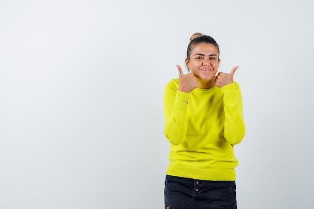 Jonge vrouw duimen opdagen met beide handen in gele trui en zwarte broek en er gelukkig uitzien
