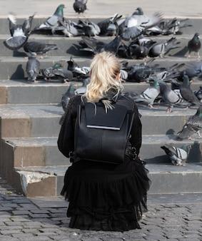 Jonge vrouw duiven voederen op het plein in het centrum van de stad uzhgorod, oekraïne